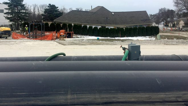 The temporary sewer bypass piping on top of 15 Mile Road near the sewer collapse, sinkhole and one of the condemned houses in Fraser on March 17, 2017.