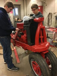 Waylon Baum, left, and Jeremy Oskey work on the restoration