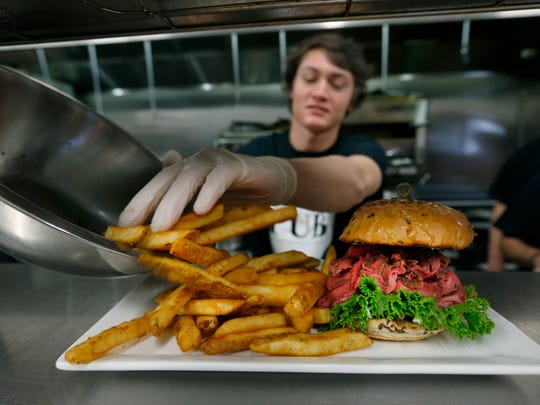 Michael Alward of Sodus adds sea salt pub fries as he puts together the Grandpa Hank's Roast Beef sandwich in the kitchen of Pub 235 in Webster.