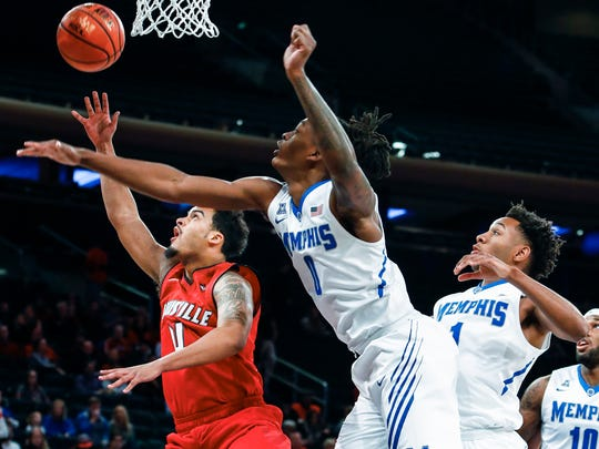 Louisville Quentin Snider (left) drives for a layup in front of Memphis defenders (left to right) Kyvon Davenport, Jamal Johnson, and Mike Parks Jr. during first half action at Madison Square Garden in New York, Saturday, December 16, 2017.