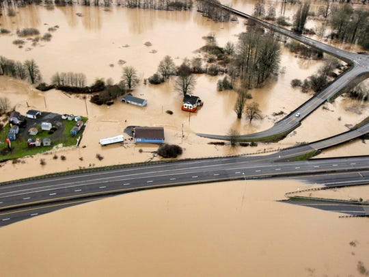 "This 2009 file photo shows Interstate 5, bottom, partially covered by floodwaters from the  Chehalis River in Chehalis, Wash. In early 2009, heavy rains and melting snow caused flooding in parts of Washington, leading to a leak in the earthen abutment of the Howard Hanson Dam. Officials in King County and several cities placed giant sandbags atop downstream levees, erected flood guards around facilities such as a jail and sewage treatment plant, and temporarily relocated the county election office. ""FEMA staff told us, `We understand why you did what you did, and it was a reasonably prudent thing to protect the public,'"" said Mark Isaacson, King County's wastewater treatment director who at the time led its flood control division. But ""it didn't fall within their definition of imminent flooding."""