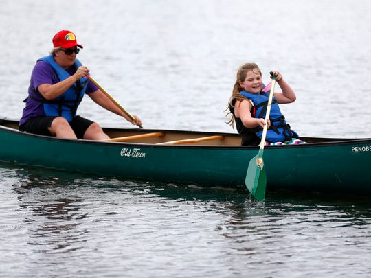 Hope Taylor, 8, paddles a canoe with Maggie Riggs,