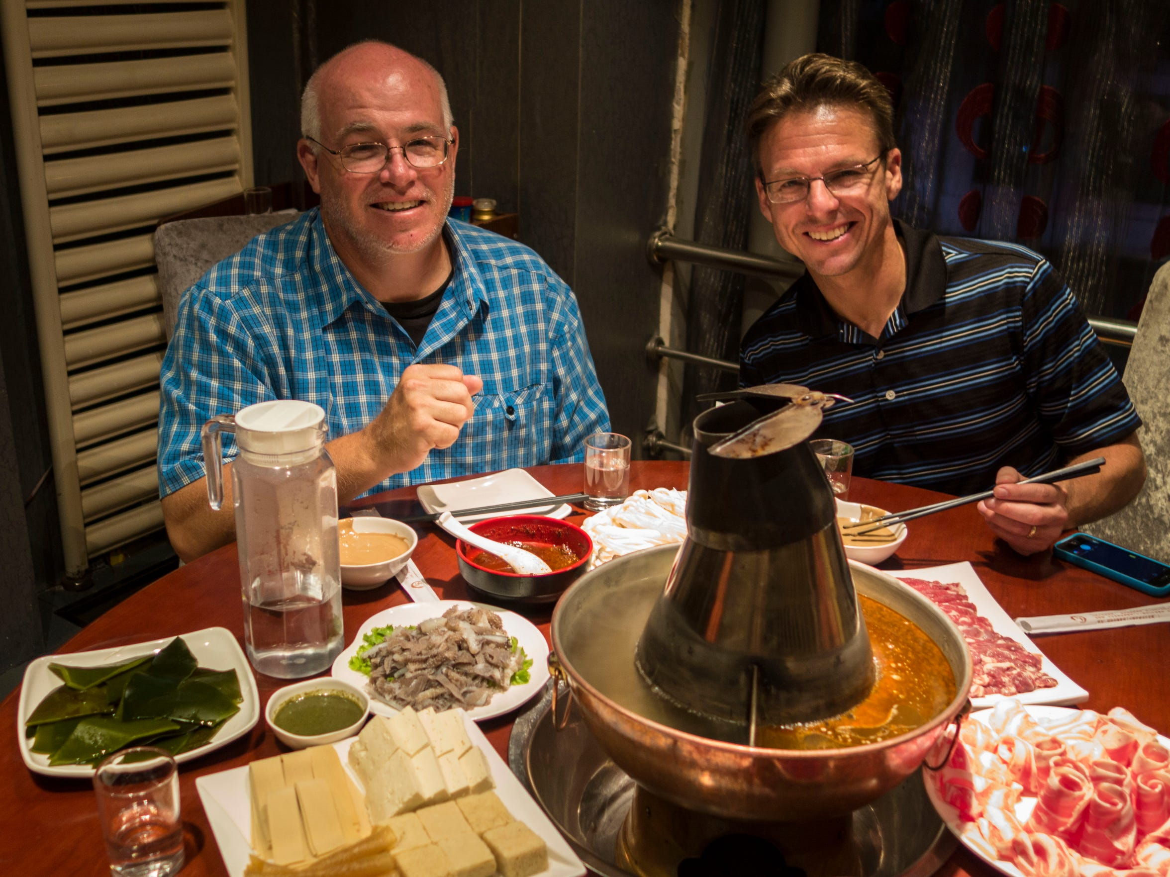 Rodney White (left) and Lynn Hicks enjoy a hot pot meal in Harbin, China, Sept. 4, 2014.