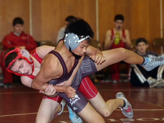 From left, Tappan Zee's Brendan Henry on his way to defeating Harrison's Daniel Choe in the 113-pound weight class during the annual Carlucci Dual Meet at Purchase College on Saturday.