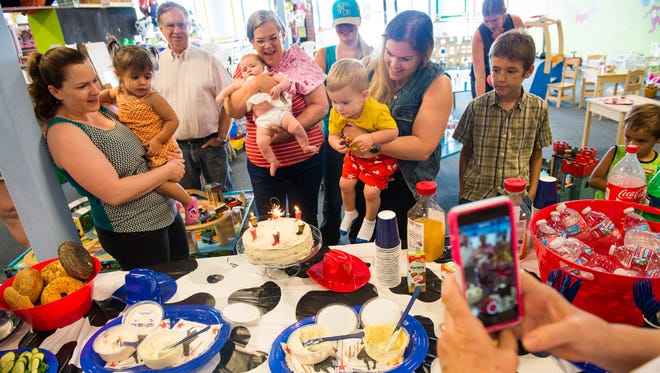 Celebrants look on as Warner Tocchini, yellow shirt, 2, prepares to blow out the candles on his birthday cake with his mother Meghan Tocchini at Playtime Oasis in Scottsdale.