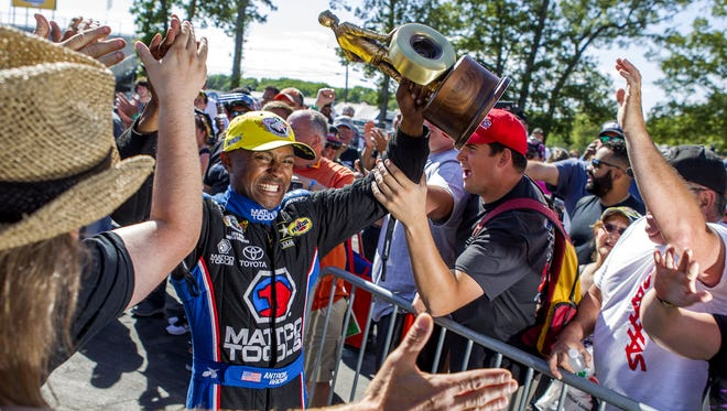 Antron Brown is greeted by fans on his way to the Winners Circle after the finals of the Toyota NHRA Summernationals at Raceway Park in Englishtown in 2015.