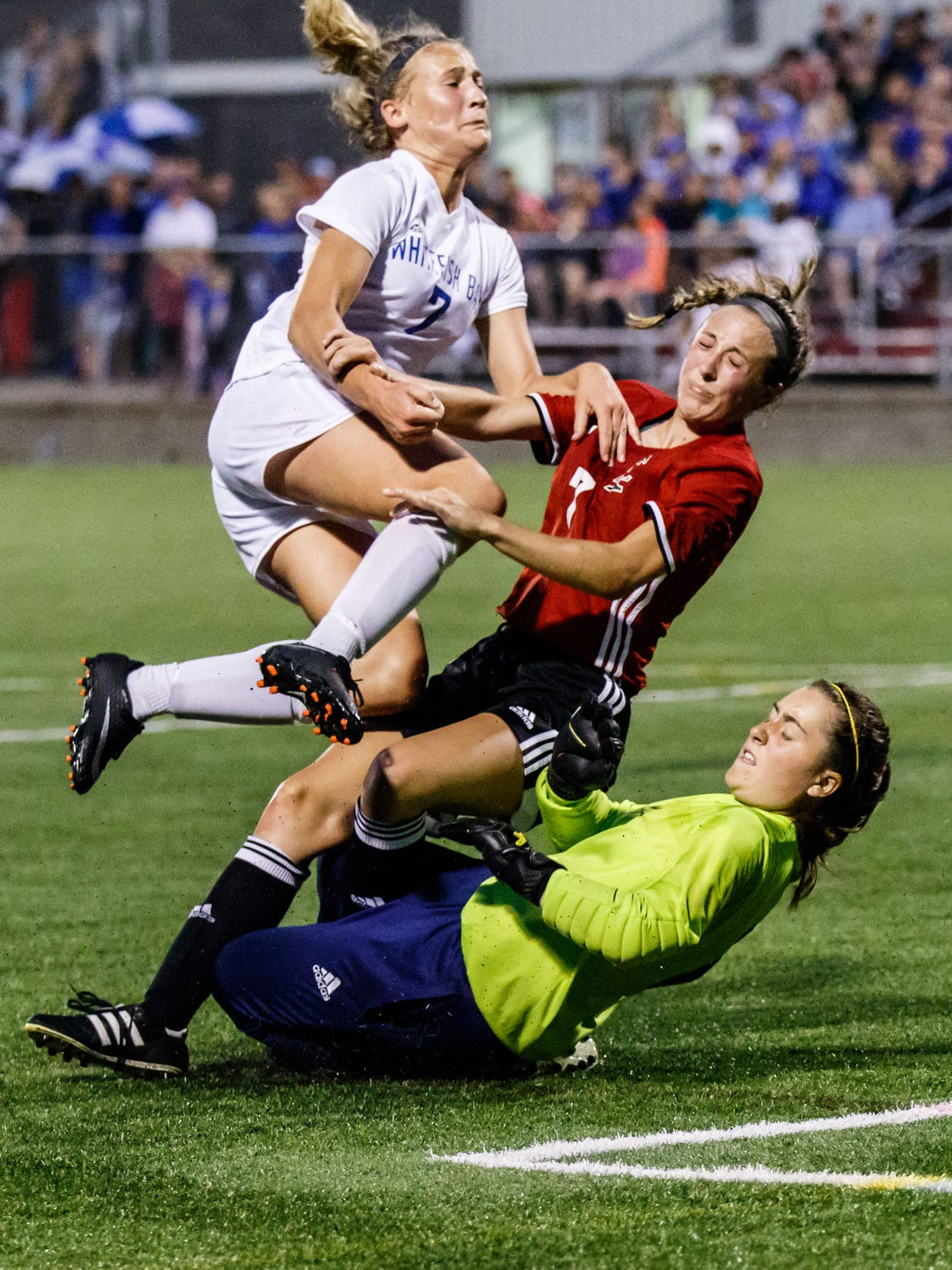 Whitefish Bay junior Gracie Riedl (top) collides with