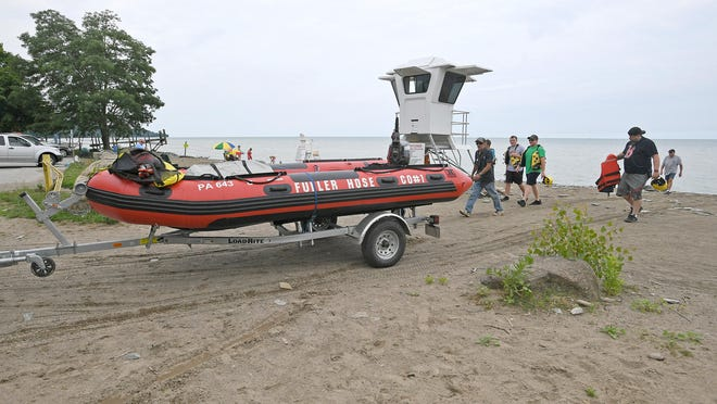 Emergency personnel from the North East Fire Department remove their rescue boat from Freeport Beach in North East Township Tuesday after rescuing two men from a capsized fishing boat about a half-mile off the beach in Lake Erie.