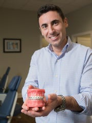 Dr. Ben Fishbein poses with a model of braces at his