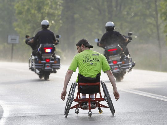 Wheelchair racer JT Michalko of Canandaigua takes off first with a police escort at the Chase Corporate Challenge at RIT.