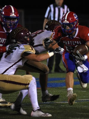 Licking Valley's Connor McLaughlin dodges Licking Heights defenders during Friday night's game. The Panthers won 33-14 and finished the regular season undefeated.