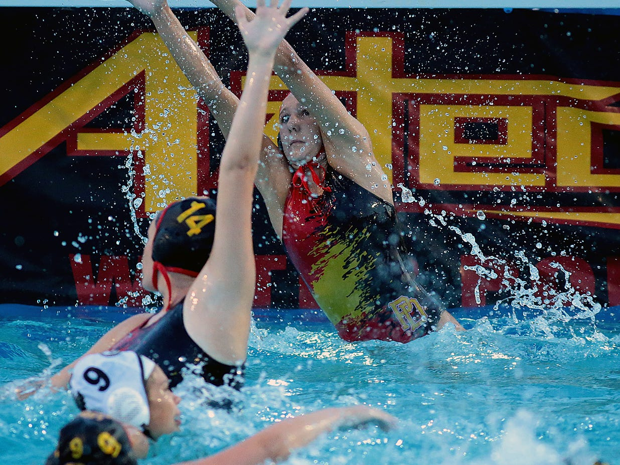 Palm Desert goalie Savannah Clyde makes a save after the shot got past teammate Megan Sawyer (14) on Wednesday. The Aztecs beat the Citrus Valley Blackhawks 14-4 in a CIF girls water polo opening-round playoff game.