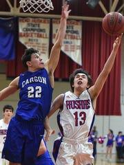 Carson's Brandon Gagnon reaches to block a shot by Carson's Christian Chamberlain Tuesday at Reno.