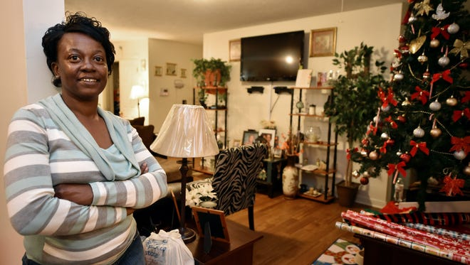 Eddie Jean Smith stands in the living room of her home in Jackson.