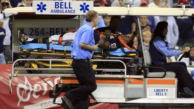 Milwaukee Brewers third baseman Elian Herrera is carted off the field after colliding with left fielder Shane Peterson while trying to catch a ball hit by Cincinnati Reds' Skip Schumaker during the eighth inning of a baseball game Saturday in Milwaukee.