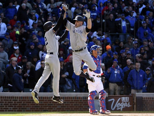 Yankees left fielder Brett Gardner (right) celebrates his three-run home run with center fielder Jacoby Ellsbury (22) against the Chicago Cubs during the ninth inning at Wrigley Field on Friday