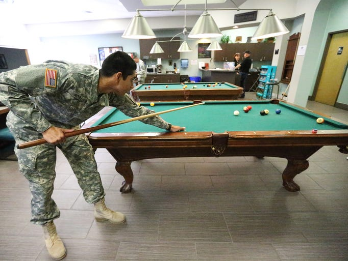 Pvt. Omar Roon enjoys a game of pool at the USO center