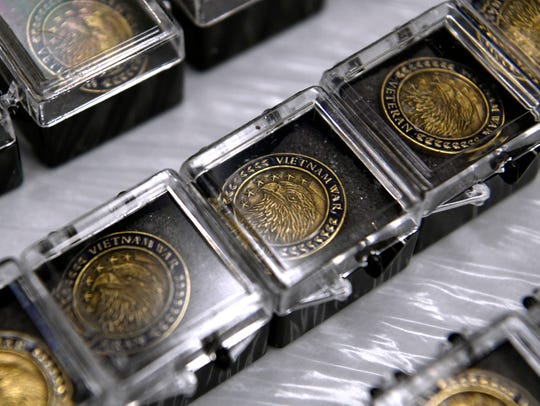 Lapel pins honoring service in the Vietnam War are lined up on a table Thursday at the Dyess Air Force Base Commissary.
