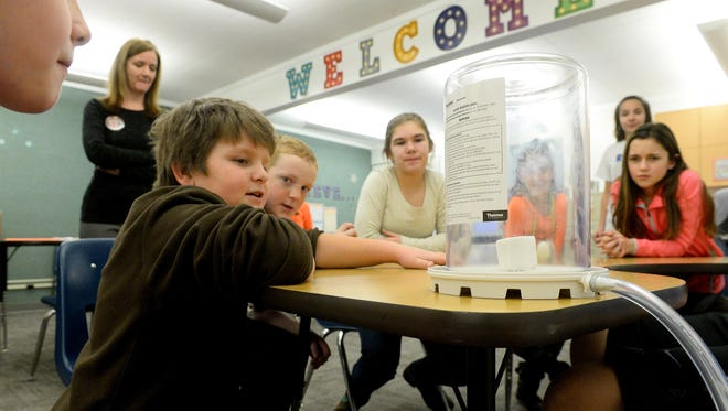 Students in Centerville's LEAP after-school program watch the effect a vacuum has on a marshmallow Tuesday afternoon. Centerville is one of nine schools in Montana chosen to work with NASA to create equipment for Mars exploration.