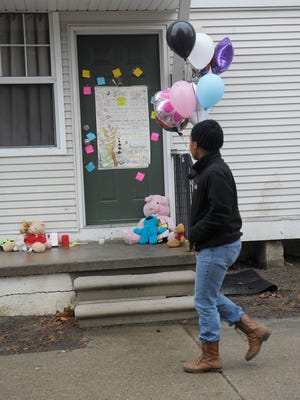 A woman walks past the apartment where the bodies of two siblings were found in freezer on Tuesday.