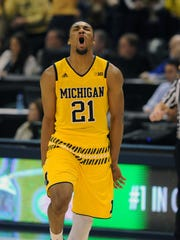 Michigan Wolverines guard Zak Irvin (21) reacts after