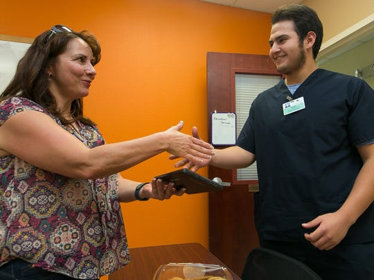 "Raul Velasquez, 18, Las Cruces Public Schools intern at Memorial Medical Center, receives an award on Friday, March 11, 2016, from LCPS EXCEL facilitator Brenda Figueroa, for his efforts during his internship. Velasquez, who is committed to becoming a doctor, is a ""Power Student"" at Las Cruces High School -- a night school program for non-traditional students."