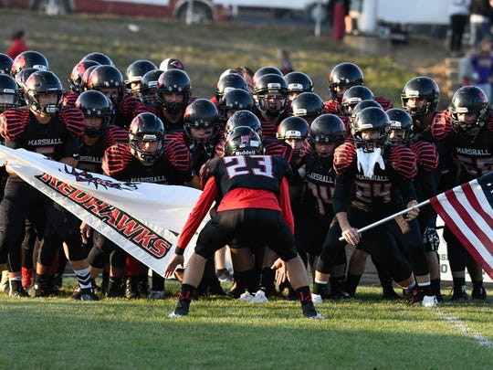 The Marshall Redhawks prepare to take the field Thursday