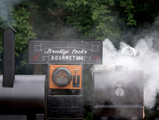Smoke billows from one of the smoking grills used in
