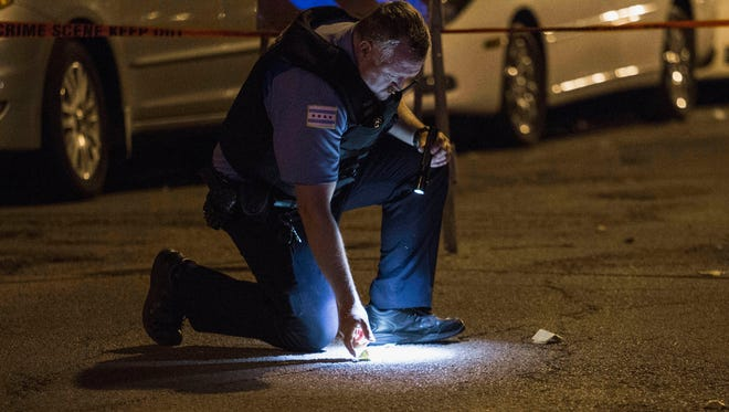 In this Sunday, July 6, 2014 photo, a Chicago police officer checks on evidence at the scene where a man was shot in Chicago's Uptown neighborhood. The Fourth of July weekend was a bloody one in Chicago, where at least nine people were shot to death and at least 60 others were wounded.