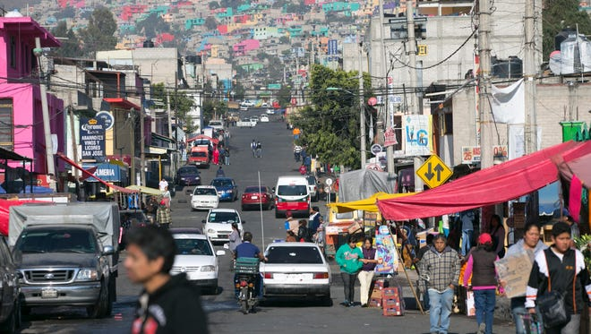 Cars, pedestrians and bikes fill the streets in a neighborhood of Ecatepec, Mexico, on Sunday, Feb. 14, 2016. Pope Francis visited the densely populated, impoverished and crime-ridden suburb of Mexico City on Sunday.