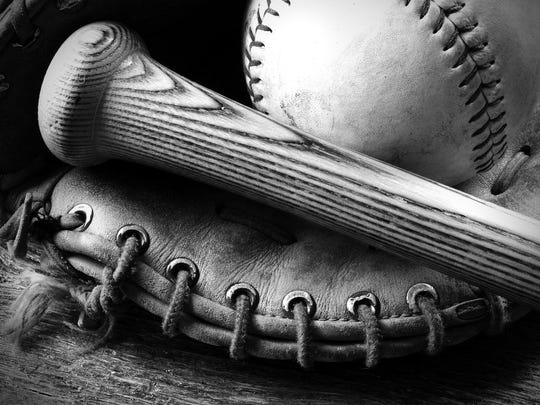 A black and white image of an old baseball glove and bat.