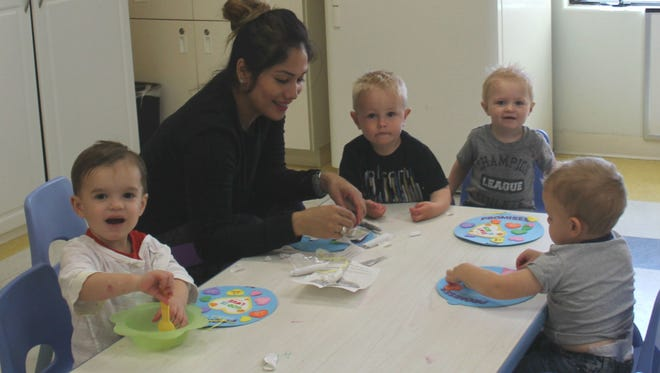 A teacher interacts with children ages 8 weeks to 5 years at a child care center.