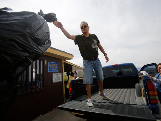 Tony Henry throws away trash April 4 at a transfer station in Shiprock.