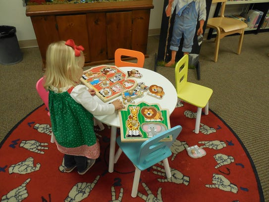 A child plays with puzzles in the children's section