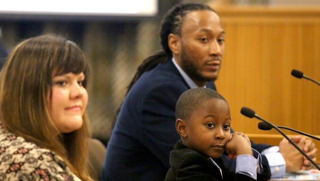 Aaron Crews, 6, sits next to his father Karanja Crews, director of Teaching With Purpose, during a hearing of the House and Senate Committee on Education at the Capitol on Tuesday, Nov. 17, 2015, in Salem, Ore.
