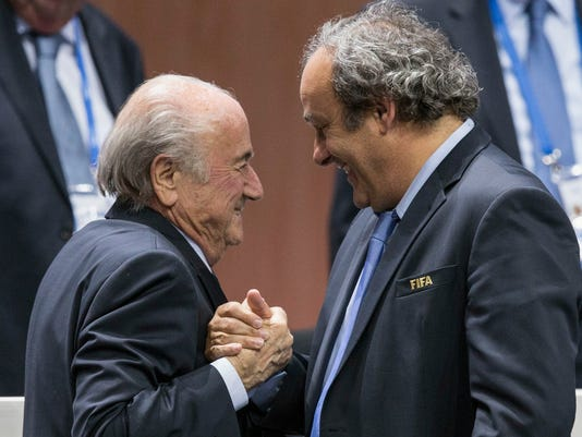 """FILE - In this Friday, May 29, 2015 file photo, FIFA president Sepp Blatter after his election as President, left is greeted by UEFA President Michel Platini, right, at the Hallenstadion in Zurich, Switzerland.  Michel Platini has launched his campaign to succeed Sepp Blatter as FIFA president, aiming to give the scandal-hit governing body """"the dignity and the position it deserves."""" Platini, the UEFA president and a FIFA vice president, wrote to member federations in Europe on Wednesday July 29, 2015 saying he will stand in the election and is counting on their support. (Patrick B. Kraemer/Keystone via AP, File)"""