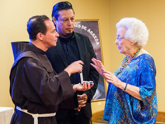 The Rev. Stefano M. Cecchin, OFM, vice postulator of the Friars Minor, presents a sacred relic of Maria de Jesus de Agreda to Tilly Chandler, chairwoman of the Lady in Blue Committee.