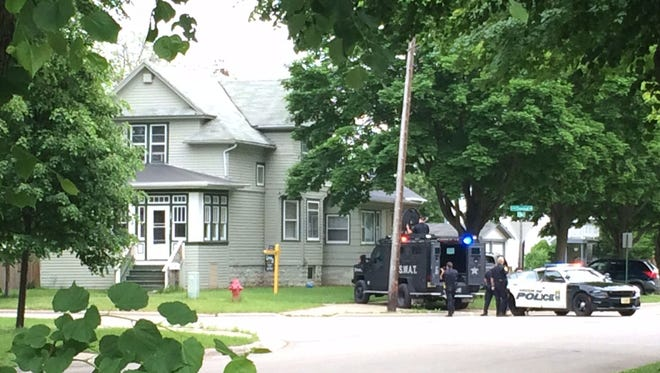 Green Bay police officers, including the SWAT team, wait outside a multifamily home at 904 N. Chestnut Ave. in Green Bay, where they apprehended a 40-year-old Green Bay man after a standoff of more than two hours Tuesday night.