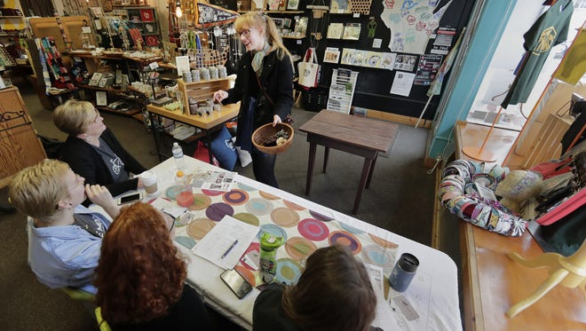Elleanor Johnson, of Appleton, shows, from left, Cathy Stratton, Isabel Garvey, Isabel Stratton, and Mia Russell, of Blue Moon Emporium, her handmade scrunchies during artist auditions at the store Monday, Jan. 23, 2017, in Appleton, Wis. Cathy Stratton, owner of Blue Moon Emporium, was holding auditions for artists with the intention of stocking her store with their art.