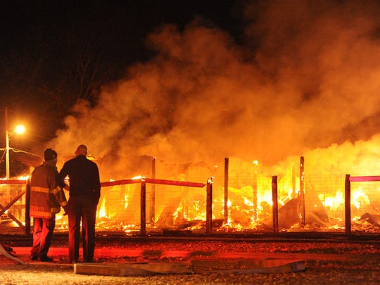 Two firefighters look over the blazing wreckage of