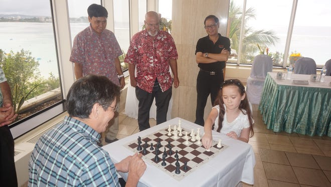 Local player Ava San Nicolas, 9, takes on grand master Eugenio Torre in the ceremonial first match of the 2015 Guam International Open Chess Tournament at the Guam Reef Hotel on Friday, July 17, 2015. San Nicolas used the English opening and Torre countered with the Grunfeld defense.