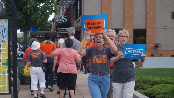 Gun safety advocates Ann Muenster, left, and Cindy Fallona march Thursday afternoon along College Avenue in downtown Appleton.