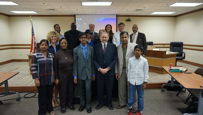 Tarandaas Anand (front row, blue shirt) is a Neville High School sophomore who found a math problem got two different answers when solved different ways. The Monroe City School Board honored him on Tuesday.