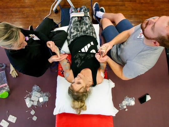 Occupational therapist Erica Albrecht and senior activity base tech Tine Richardson stimulate the arms of Amy Bailey with an electrical current during a therapy session.  Dec. 12, 2016