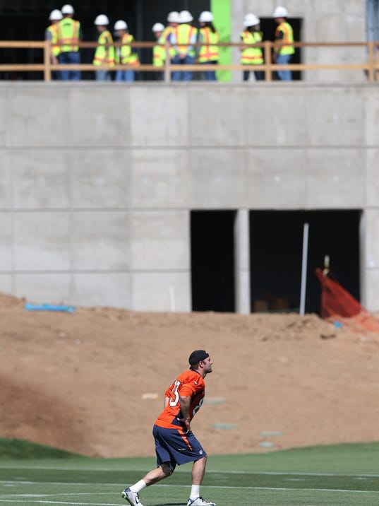 As construction workers look on from a new facility being built at the team's headquarters, Denver Broncos wide receiver Wes Welker, front, runs during a morning session at the team's NFL football training camp in Englewood, Colo.,  on Friday, July 25, 2014. Because of the construction, the Broncos will practice without the usual cadre of fans looking on as the team prepares for the upcoming NFL season. (AP Photo)
