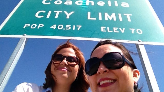 """Desert Sun reporters Paulina Rojas, left and Xochitl Peña right pose for a selfie in front of the sign used by Beyoncè and Nicki Minaj in the """"Feeling Myself"""" video."""