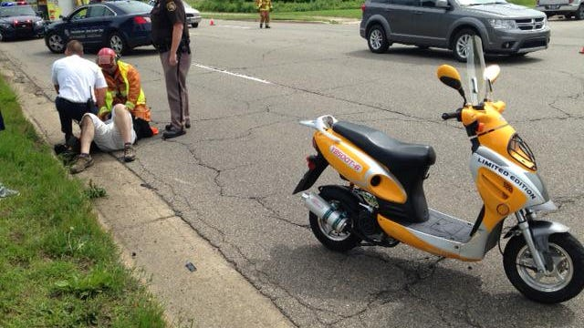 Emergency crews work on a scooter crash victim Wednesday morning on Helmer Road.