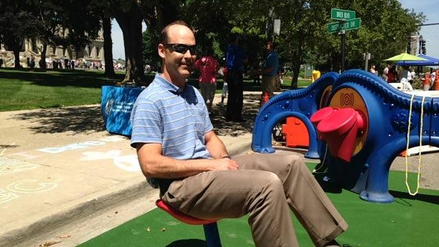 """Andy Kilpatrick, transportation engineer for the city of Lansing, takes a spin on Capitol Avenue. Around 18 parking spaces and the west traffic lane were converted into """"parklets"""" for the public to enjoy."""