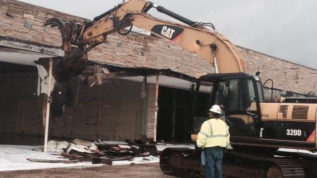 Berkeley Mayor Carmen A. Amato Jr. uses a backhoe to start demolition at the Beachwood Shopping Center Tuesday morning.