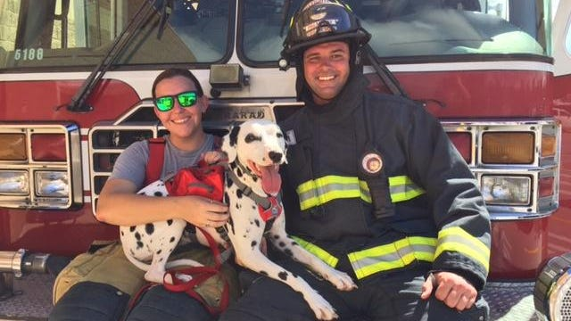 Palm Bay Fire Rescue firefighters Alexandra Gray and Jacob Couture hang out with Lucy, a Dalmatian.